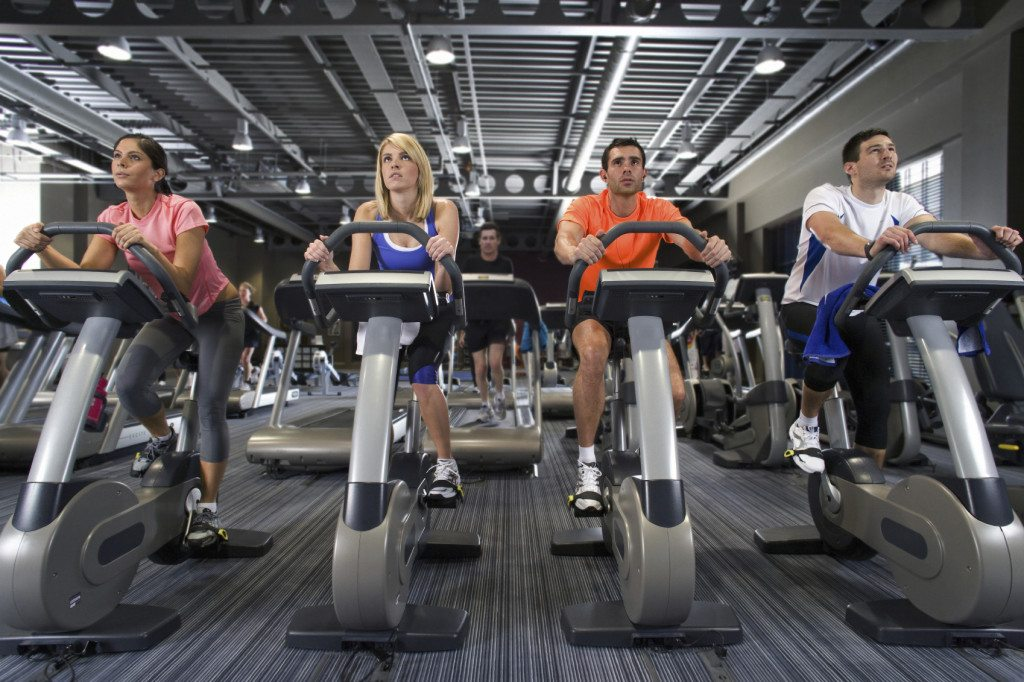 Men and women riding exercise bikes in health club